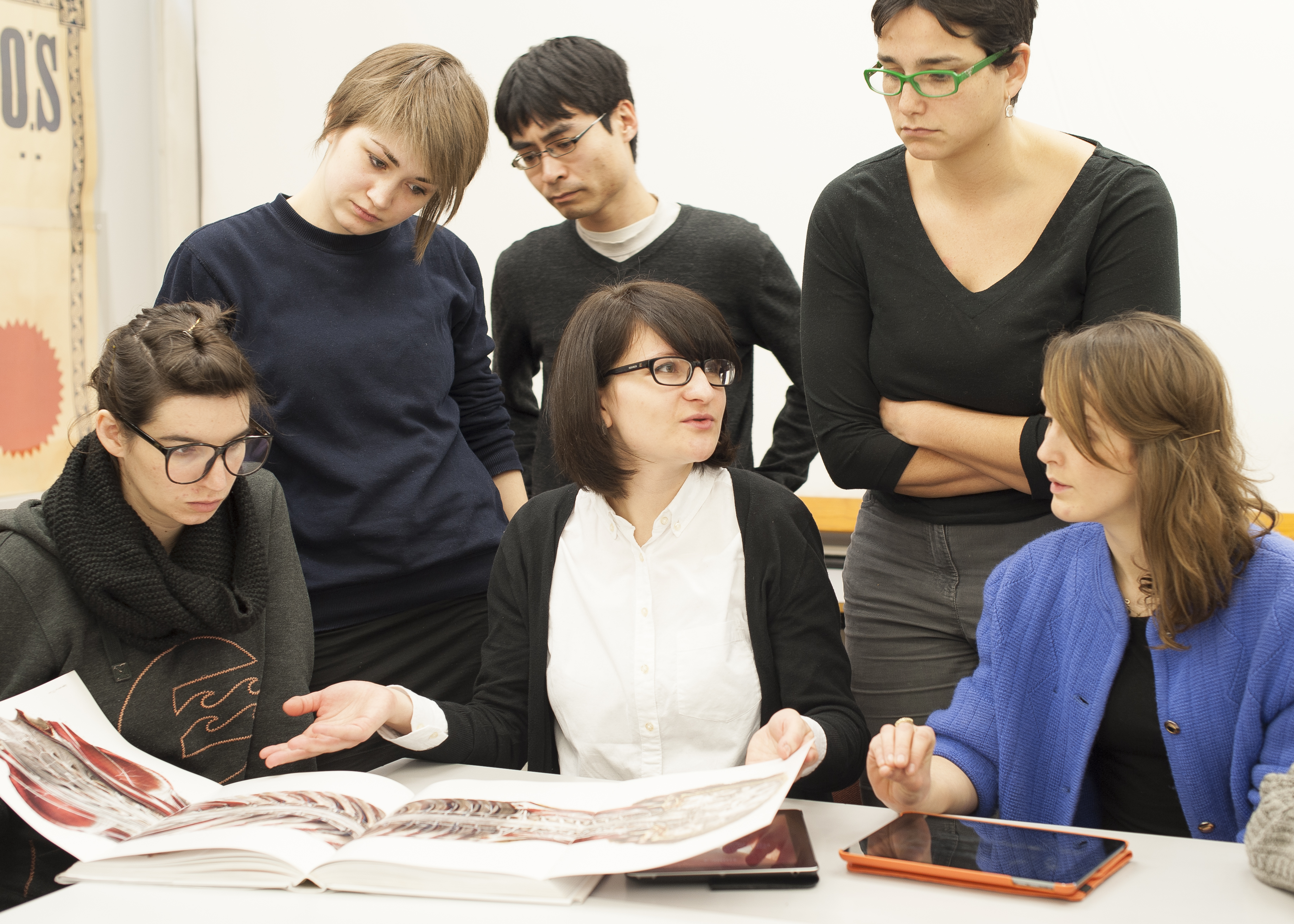 A group of five postgraduate students with a tutor looking at publishing projects